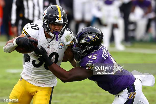 Running back James Conner of the Pittsburgh Steelers is tackled by linebacker Jaylon Ferguson of the Baltimore Ravens in the third quarter at M&T...