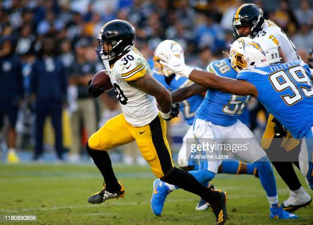 Running back James Conner of the Pittsburgh Steelers runs the ball between outside linebacker Thomas Davis and defensive tackle Jerry Tillery of the...