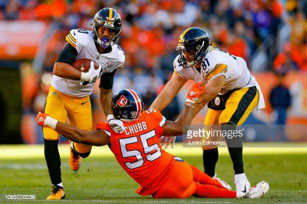 Running back James Conner of the Pittsburgh Steelers runs through a tackle attempt by outside linebacker Bradley Chubb of the Denver Broncos in the...