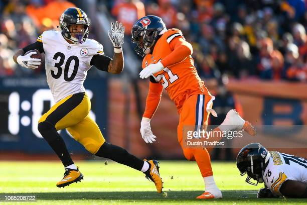 Running back James Conner of the Pittsburgh Steelers rushes against the Denver Broncos as Todd Davis attempts a tackle in the first quarter of a game...