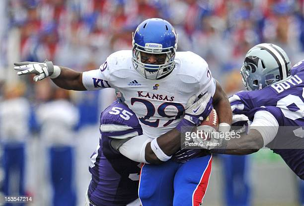 Running back James Sims of the Kansas Jayhawks rushes against pressure from defenders Javonta Boyd and Adam Davis of the Kansas State Wildcats during...