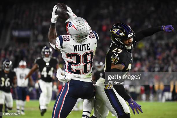 Running back James White of the New England Patriots makes a catch in front of safety Earl Thomas III of the Baltimore Ravens during the second...