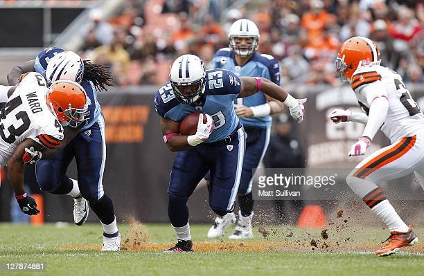 Running back Jamie Harper of the Tennessee Titans runs by defenders TJ Ward and Joe Haden of the Cleveland Browns at Cleveland Browns Stadium on...