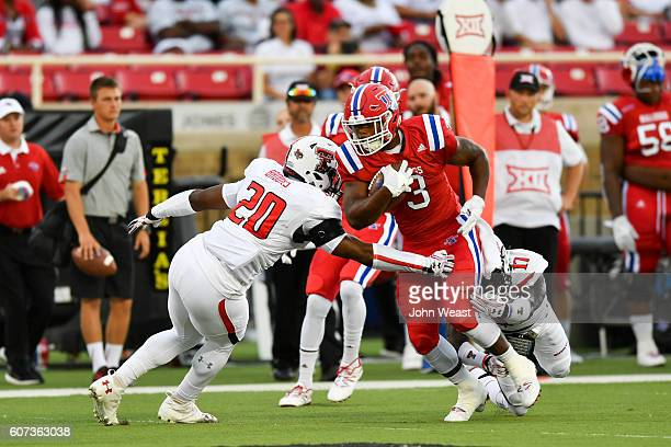 Running back Jarred Craft of the Louisiana Tech Bulldogs runs through the tackles of linebacker Jordyn Brooks of the Texas Tech Red Raiders and...
