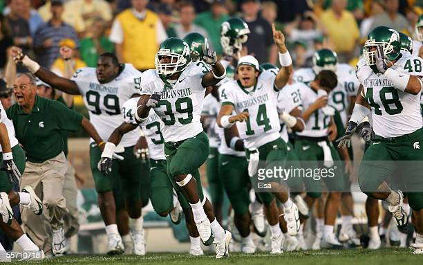 Running back Javon Ringer of the Michigan State Spartans leads the bench onto the field in celebration after defeating the Notre Dame Fighting Irish...