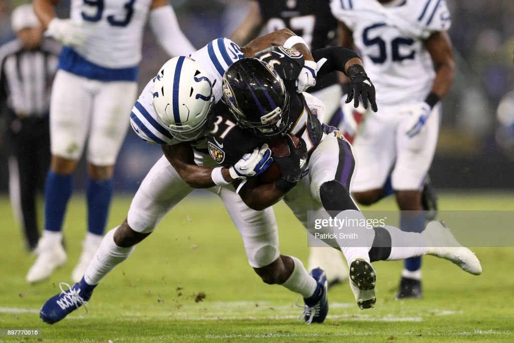 Running Back Javorius Allen #37 of the Baltimore Ravens carries the ball as he is tackled by free safety T.J. Green #32 of the Indianapolis Colts in the third quarter at M&T Bank Stadium on December 23, 2017 in Baltimore, Maryland.