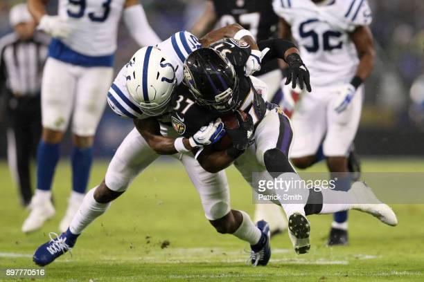 Running Back Javorius Allen of the Baltimore Ravens carries the ball as he is tackled by free safety TJ Green of the Indianapolis Colts in the third...