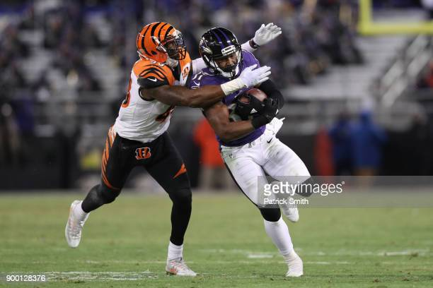 Running Back Javorius Allen of the Baltimore Ravens carries the ball as he is tackled by free safety George Iloka of the Cincinnati Bengals in the...