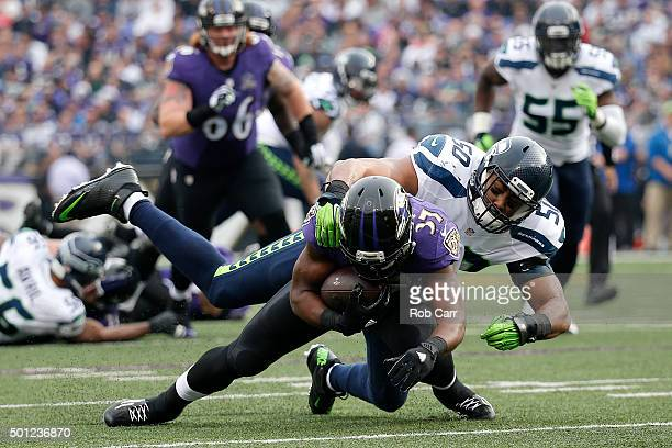 Running back Javorius Allen of the Baltimore Ravens is tackled by outside linebacker KJ Wright of the Seattle Seahawks in the second quarter at MT...