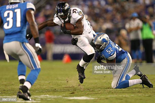 Running back Javorius Allen of the Baltimore Ravens is tackled by linebacker Antwione Williams of the Detroit Lions during the second half in their...