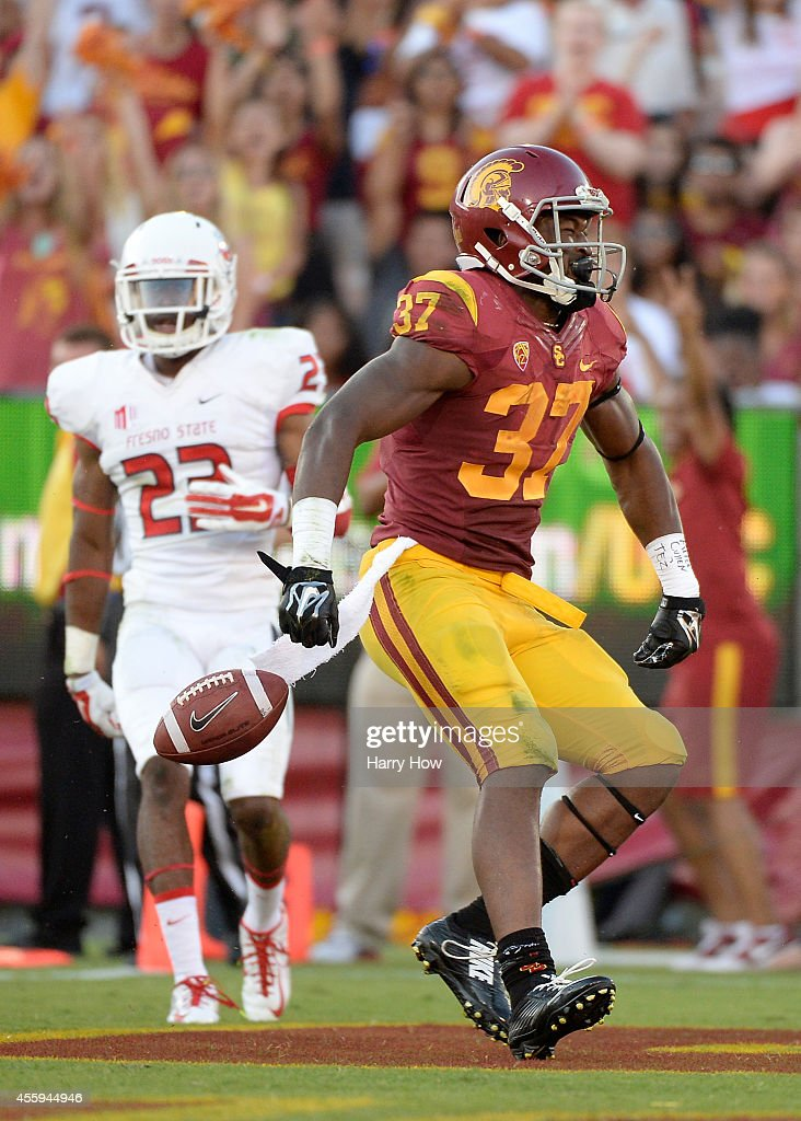 Running back Javorius Allen #37 of the USC Trojans reacts to his touchdown for a 38-13 lead in front of defensive back Bryan Harper #23 of Fresno State Bulldogs during the third quarter at Los Angeles Memorial Coliseum on August 30, 2014 in Los Angeles, California.