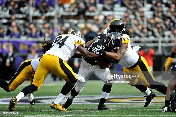 Running back Javorius 'Buck' Allen of the Baltimore Ravens is tackled by linebackers Jarvis Jones and Lawrence Timmons of the Pittsburgh Steelers...