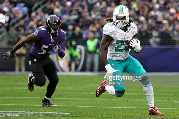 Running back Jay Ajayi of the Miami Dolphins carries the ball past inside linebacker Zach Orr of the Baltimore Ravens in the first quarter at MT Bank...