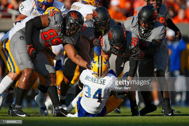 Running back J'Cobi Skinner of the McNeese State Cowboys gets taken down by safety Malcolm Rodriguez defensive end Tyler Lacy safety Kolby...