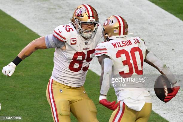 Running back Jeff Wilson Jr. #30 celebrates with tight end George Kittle of the San Francisco 49ers after Wilson's touchdown during the first half...