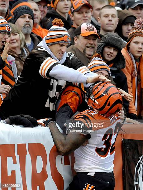 Running back Jeremy Hill of the Cincinnati Bengals attempting to jump into the crowd after scoring a touchdown is denied by a Cleveland Browns fan...