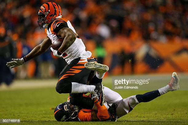 Running back Jeremy Hill of the Cincinnati Bengals is tackled by free safety Bradley Roby of the Denver Broncos during a game at Sports Authority...