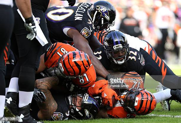 Running back Jeremy Hill of the Cincinnati Bengals is tackled by strong safety Eric Weddle outside linebacker Albert McClellan of the Baltimore...