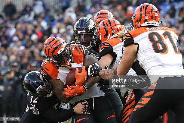Running back Jeremy Hill of the Cincinnati Bengals is tackled by strong safety Eric Weddle of the Baltimore Ravens in the second quarter at MT Bank...