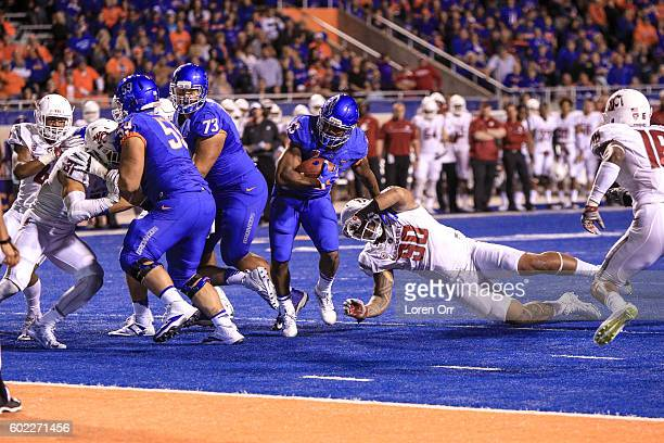 Running back Jeremy McNichols of the Boise State Broncos pushes through the tackle of defensive lineman Daniel Ekuale of the Washington State Cougars...
