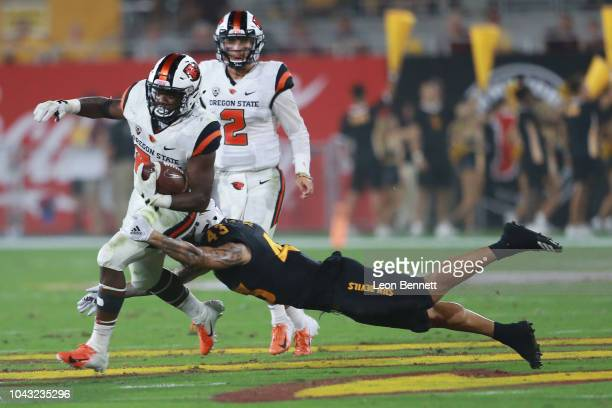 Running back Jermar Jefferson of the Oregon State Beavers carries the ball against Safety Jalen Harvey of the Arizona State Sun Devils at Sun Devil...