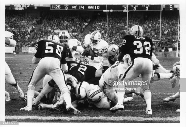 Running back Jess Phillips of the New England Patriots scores a touchdown against linebacker Monte Johnson defensive lineman John Matuszak and...