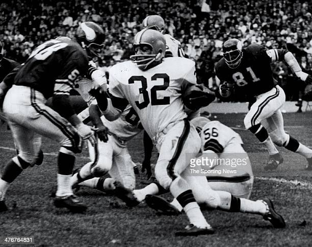 Running Back Jim Brown of the Cleveland Browns against Carl Eller and Rip Hawkins of the Minnesota Vikings circa 1964 at Cleveland Municipal Stadium...