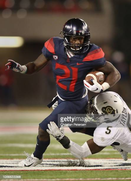 Running back JJ Taylor of the Arizona Wildcats rushes the football against linebacker Davion Taylor of the Colorado Buffaloes during the second half...