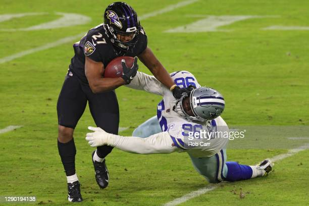 Running back J.K. Dobbins of the Baltimore Ravens stiff arms defensive tackle Neville Gallimore of the Dallas Cowboys during the fourth quarter at...