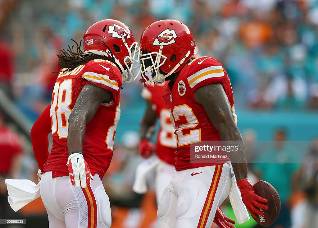 Running back Joe McKnight #22 of the Kansas City Chiefs celebrates with Junior Hemmingway #88 after scoring a third-quarter touchdown against the Miami Dolphins at Sun Life Stadium on September 21, 2014 in Miami Gardens, Florida.