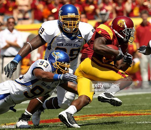 Running back Joe McKnight of the USC Trojans carries the ball against linebacker Justin Cole and defensive tackle Justin Willis of the San Jose State...