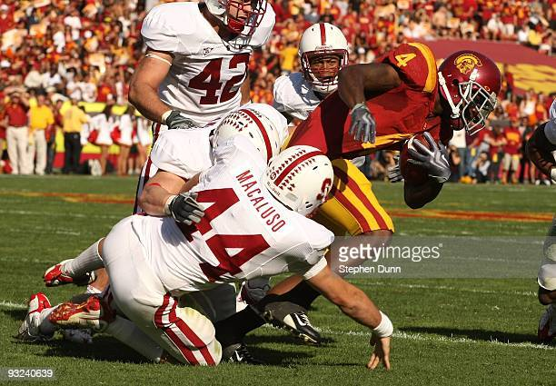 Running back Joe McKnight of the USC Trojans is tackled by linebacker Nick Macaluso of the Stanford Cardinal on November 14 2009 at the Los Angeles...