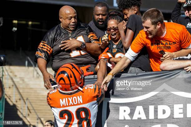 Running back Joe Mixon of the Cincinnati Bengals hands a football to his mother Alisa Mixon after scoring a touchdown against the Oakland Raiders...