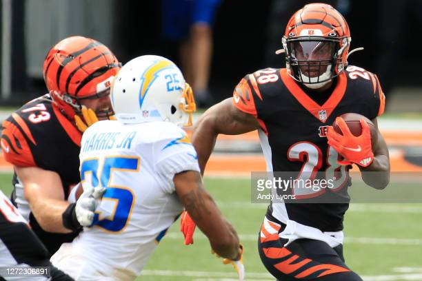 Running back Joe Mixon of the Cincinnati Bengals rushes in front of cornerback Chris Harris of the Los Angeles Chargers during the first half at Paul...