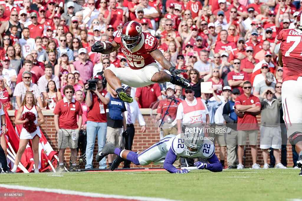 Running back Joe Mixon #25 of the Oklahoma Sooners leaps over safety Dante Barnett #22 of the Kansas State Wildcats for a first half touchdown at Gaylord Family Oklahoma Memorial Stadium on October 15, 2016 in Norman, Oklahoma.