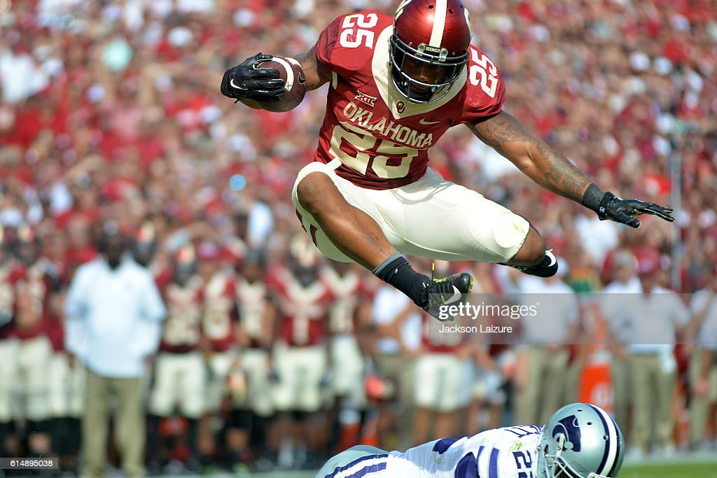 Running back Joe Mixon #25 of the Oklahoma Sooners leaps over safety Dante Barnett #22 of the Kansas State Wildcats on Saturday October 15, 2016 at Gaylord Family Oklahoma Memorial Stadium in Norman, Oklahoma.