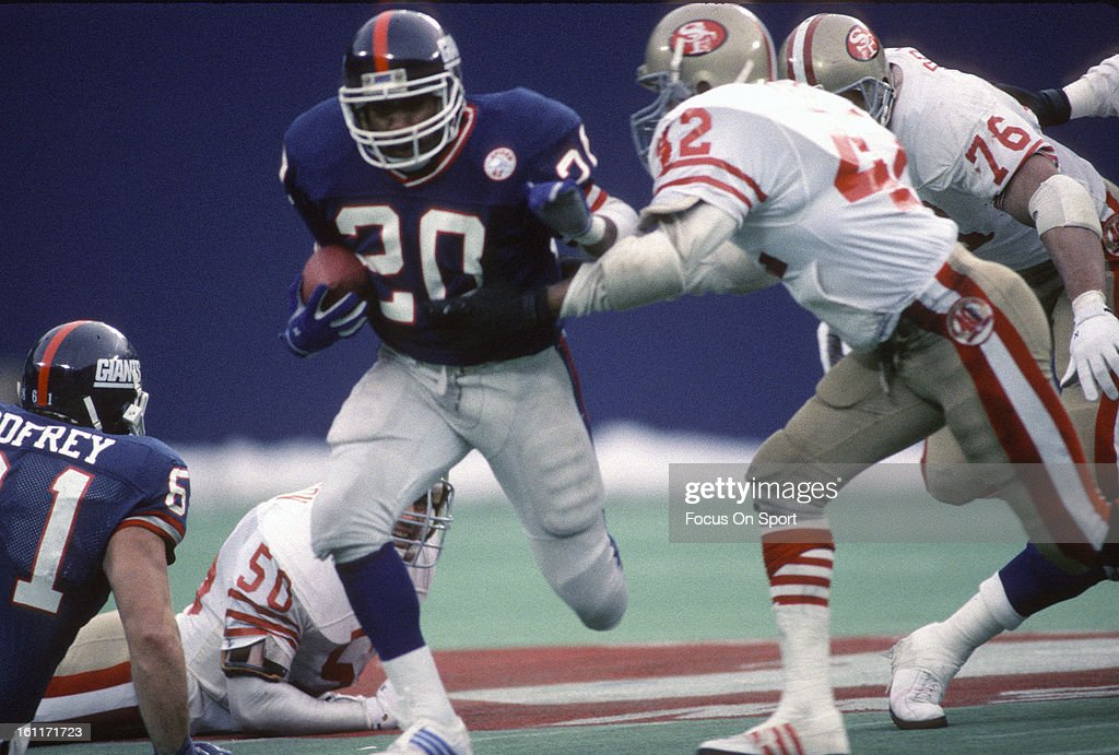 Running back Joe Morris of the New York Giants looks to break the tackle of Ronnie Lott of the San Francisco 49ers during the NFC Divisional Playoff...