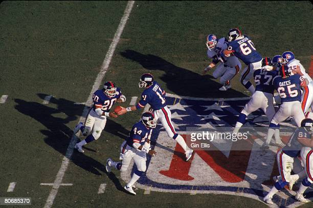 Running back Joe Morris of the New York Giants takes a handoff from quarterback Phil Simms on a flea flicker play against the Denver Broncos in Super...