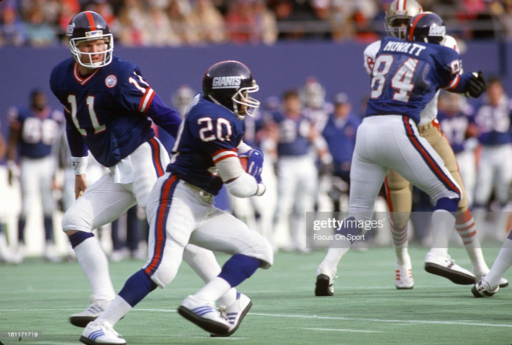 Running back Joe Morris of the New York Giants takes the handoff from quarterback Phil Simms against the San Francisco 49ers during the NFC...