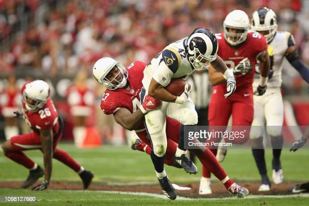Running back John Kelly of the Los Angeles Rams is tackled by outside linebacker Haason Reddick of the Arizona Cardinals during the NFL game at State...