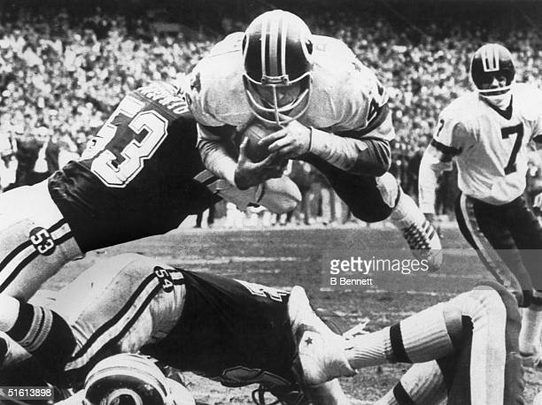 Running back John Riggins of the Washington Redskins goes up and over Randy White and Bob Breunig of the Dallas Cowboys for the Redskins second...