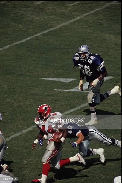 Running back John Settle of the Atlanta Falcons runs away from safety Bill Bates of the Dallas Cowboys in Atlanta FultonCounty Stadium on September...