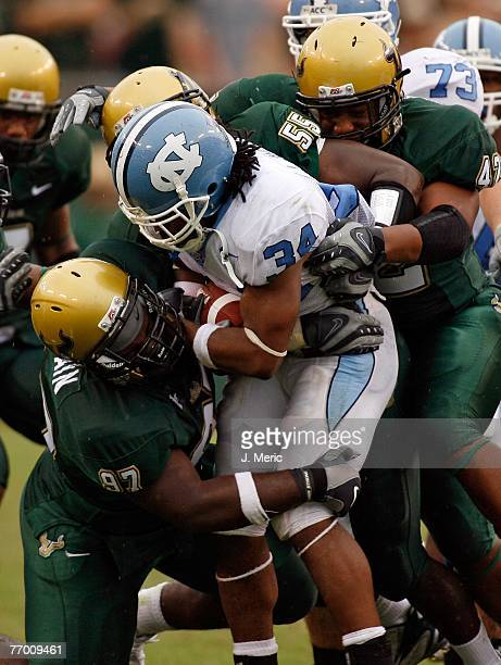 Running back Johnny White of the North Carolina Tar Heels looks for some yards as Defensive lineman Terrell McClain Linebacker Donte Spires and...