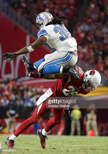 Running back Joique Bell of the Detroit Lions jumps over free safety Rashad Johnson of the Arizona Cardinals as he rushes the football during the...