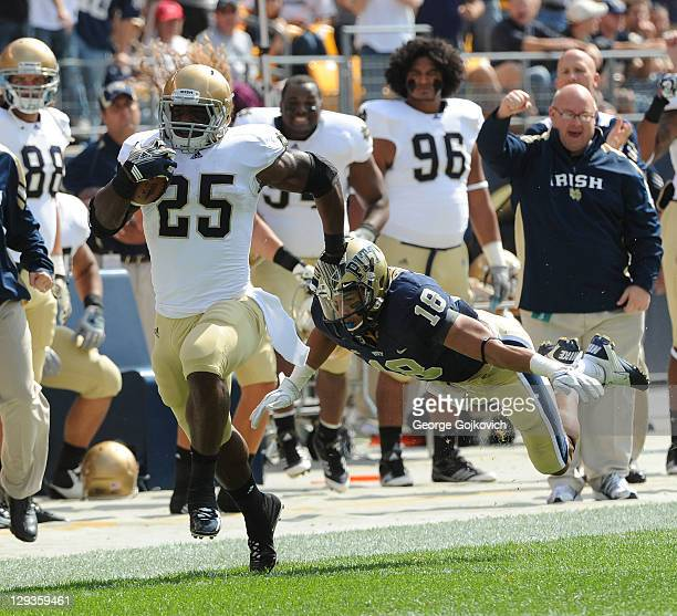 Running back Jonas Gray of the Notre Dame Fighting Irish eludes safety Jarred Holley of the University of Pittsburgh Panthers as he makes a 79yard...