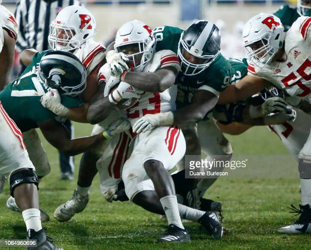 Running back Jonathan Hilliman of the Rutgers Scarlet Knights is tackled by defensive tackle Raequan Williams of the Michigan State Spartans and...