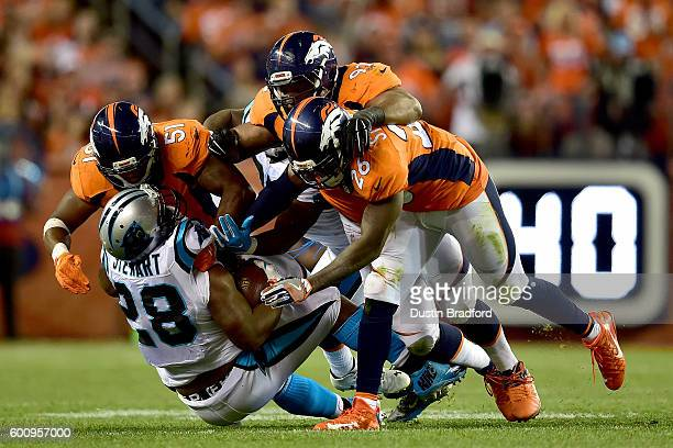 Running back Jonathan Stewart of the Carolina Panthers is tackled by three Denver Broncos defenders in the second half at Sports Authority Field at...