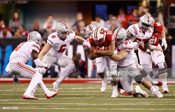 Running back Jonathan Taylor of the Wisconsin Badgers is tackled by defensive lineman Nick Bosa of the Ohio State Buckeyes during the Big Ten...