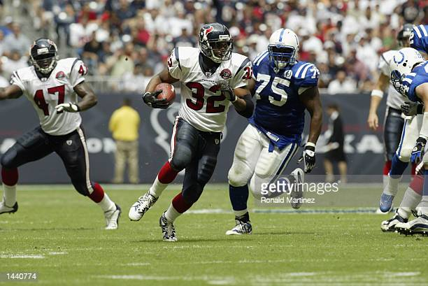Running back Jonathan Wells of the Houston Texans runs the ball as defensive tackle Larry Tripplett of the Indianaplis Colts chases after him during...