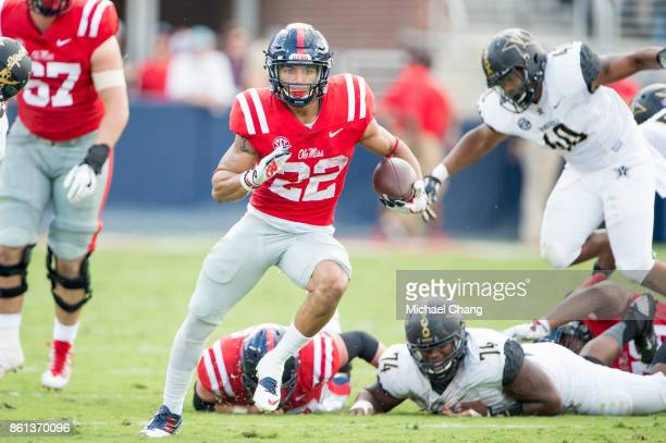 Running back Jordan Wilkins of the Mississippi Rebels runs the ball after escaping a tackle by defensive lineman Jay Woods of the Vanderbilt...